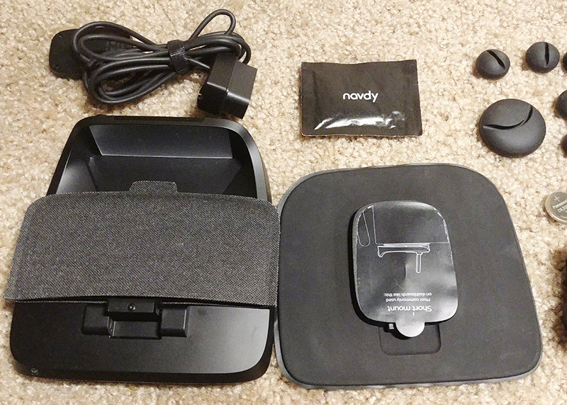 The Navdy system includes a dongle (the item on the top left), which uses a wire to transmit data from the vehicle's computer to the heads-up display.